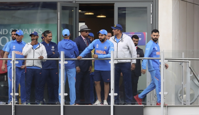 India's captain Virat Kohli, right, stands in the pavilion with teammates after their team lost the Cricket World Cup semifinal match between India and New Zealand at Old Trafford in Manchester, Wednesday, July 10, 2019.