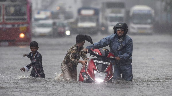 Commuters wade through a waterlogged street during heavy monsoon rain in Mumbai's Ghatkopar  on Tuesday, 2 July.