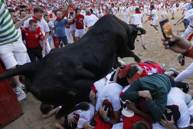 A cow jumps over revellers following the running of the bulls at the San Fermin Festival, in Pamplona.
