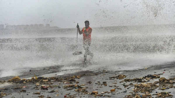 A civic worker clears the plastic waste and garbage thrown out of the sea during a high tide at Marine Drive promenade in Mumbai, on Sunday, 7 July.