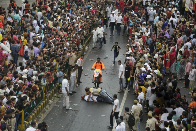 A man performs a bike stunt during the annual festival of Rath Yatra.