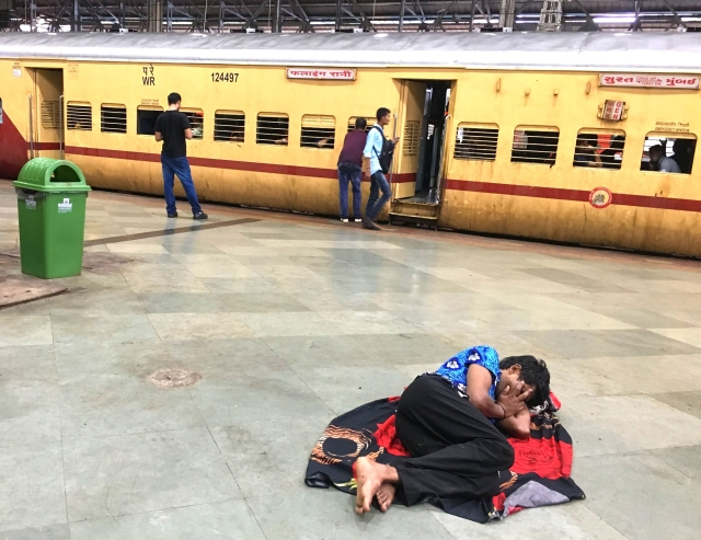 Trains arrive and leave, while this man curls in sleep on the Mumbai Central platform.
