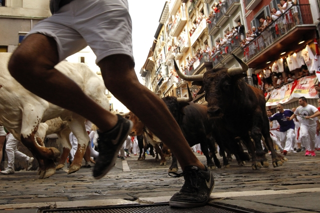 People run next to fighting bulls from Cebada Gago ranch, during the running of the bulls at the San Fermin Festival, in Pamplona.