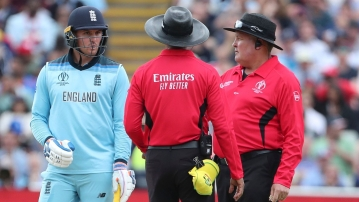 England's Jason Roy, left, interacts with the umpires after he was given out during the Cricket World Cup semi-final match between England and Australia at Edgbaston in Birmingham, England, Thursday, July 11, 2019.