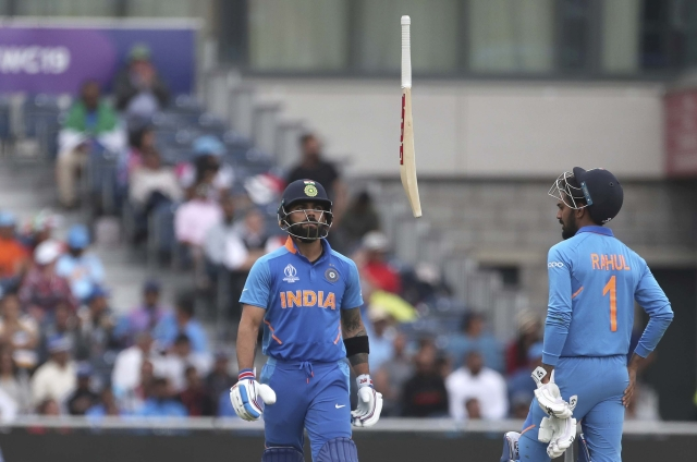 Virat Kohli (L) throws his bat in frustration after being dismissed by New Zealands Trent Boult.