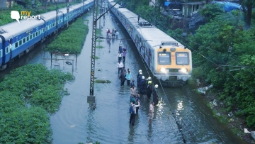 People walk on railway tracks as heavy rainfall disrupts railway service.