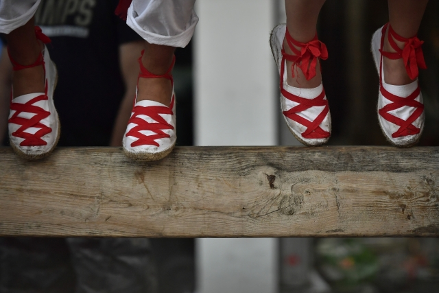 Revellers sit atop of a wooden barrier during the running of the bulls at the San Fermin Festival, in Pamplona.