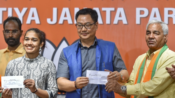 Union Minister Kiren Rijiju offers membership slip to wrestler Babita Phogat and her father Mahavir Singh Phogat as they join the BJP at party headquarters  in New Delhi.