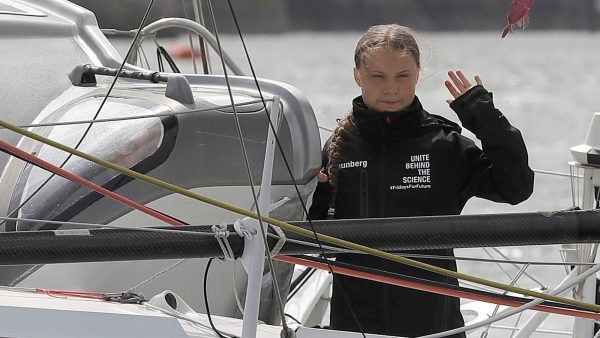 In this 14 August, 2019 file photo, Climate change activist Greta Thunberg waves from the Malizia II boat in Plymouth, England.
