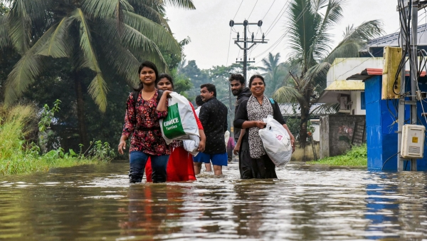Villagers wade through a waterlogged street in Ernakulam