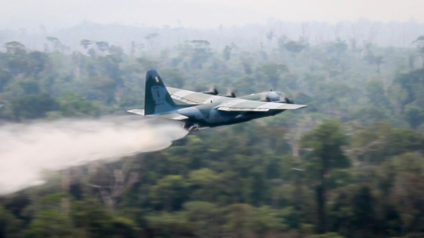 In this photo released by Brazil Ministry of Defense, a C-130 Hercules aircraft dumps water to fight fires burning in the Amazon rainforest, in Brazil.