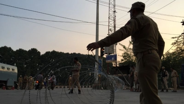 A security personnel putting up a barbwire fence to cordon off a street in Srinagar.