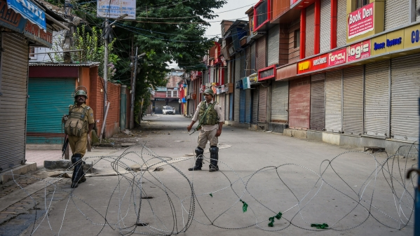 Security personnel stand guard during restrictions in Srinagar on 12 August.