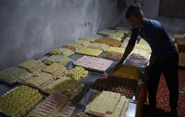 An Indian vendor displays sweets for sale on Diwali, in Uttar Pradesh's Ayodhya.