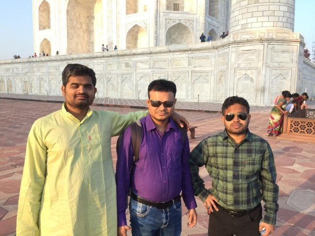 Basanta Behera, Ananta Kumar Nayak, and Amit Kumar Mohanty pose in front of the Taj Mahal.