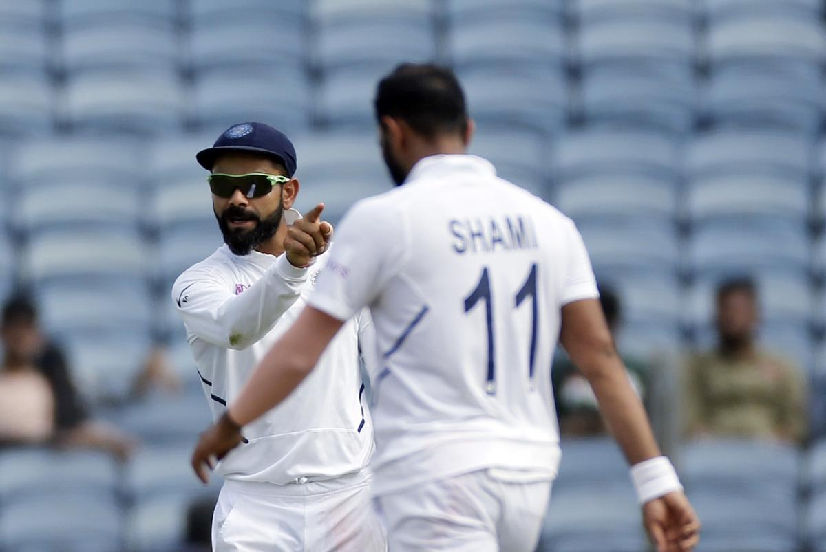 Indian cricket team captain Virat Kohli celebrates a wicket with Mohammed Shami.
