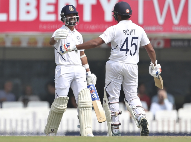 India's Ajinkya Rahane, left, celebrates with batting partner Rohit Sharma after scoring a century during the second day of third and last cricket test.