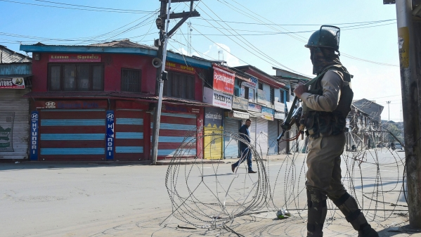 A security personnel stands guard during restrictions, in Srinagar. Mobile postpaid connectivity will be restored today, the J&K administration has said.