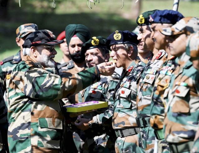 Prime Minister Narendra Modi feeds sweets to Indian Army personnel during Diwali celebrations in Rajouri district, Jammu and Kashmir. PM Modi was in Rajouri for Diwali, to meet with jawans on duty.