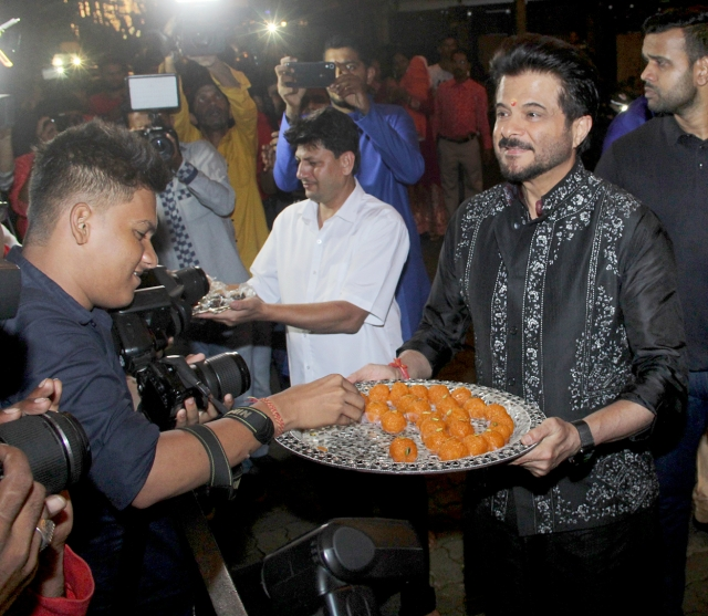 Anil Kapoor offering <i>laddoos</i> to the media outside his home.