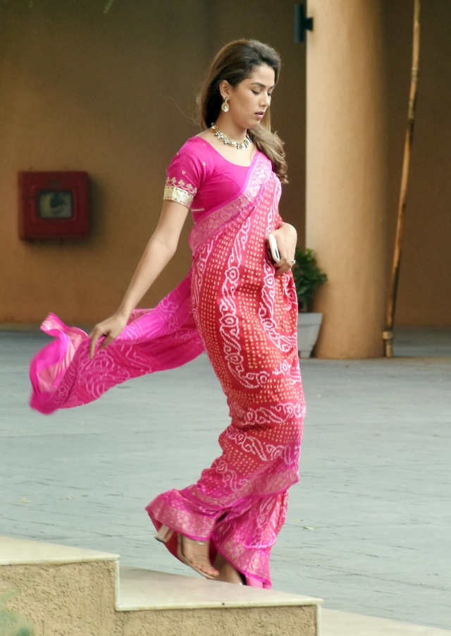 Mira Kapoor is dressed in a bright pink saree.