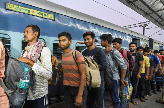 Workers arrive at the station from Jammu and Kashmir, in Kolkata.