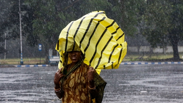 A woman covers her head with a plastic sheet as it rained in Kolkata.