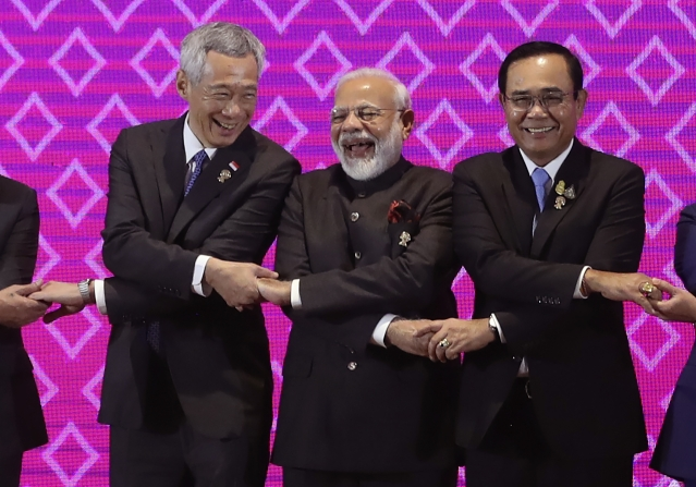 India's Prime Minister Narendra Modi, center, laughs as he poses for a group photo with Singapore Prime Minister Lee Hsien Loong, left, and Thailand Prime Minister Prayuth Chan-ocha during The Association of Southeast Asian Nations ASEAN-India summit in Nonthaburi, Thailand.