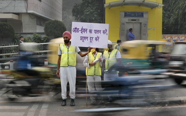 Volunteers wear pollution masks as they stand at a busy crossing with the banner saying obey odd and even, remove pollution, in New Delhi.