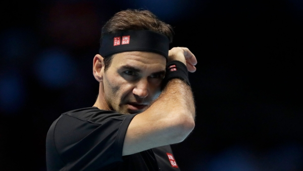 Roger Federer of Switzerland wipes his face after he plays a return to Stefanos Tsitsipas of Greece during their ATP World Tour Finals semifinal tennis match at the O2 Arena in London, Saturday.