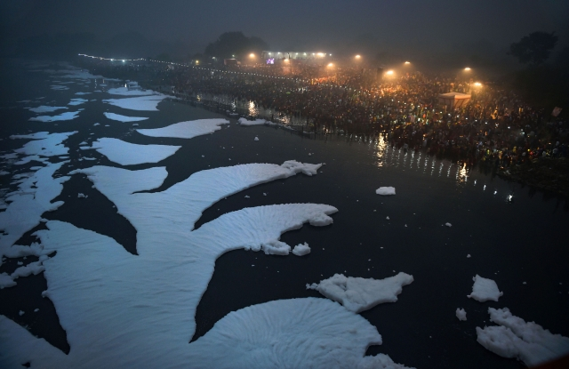 Devotees offers prayers as toxic foam floats on the surface of polluted Yamuna river during Chhath Puja celebrations, at Kalindi Kunj, in New Delhi.
