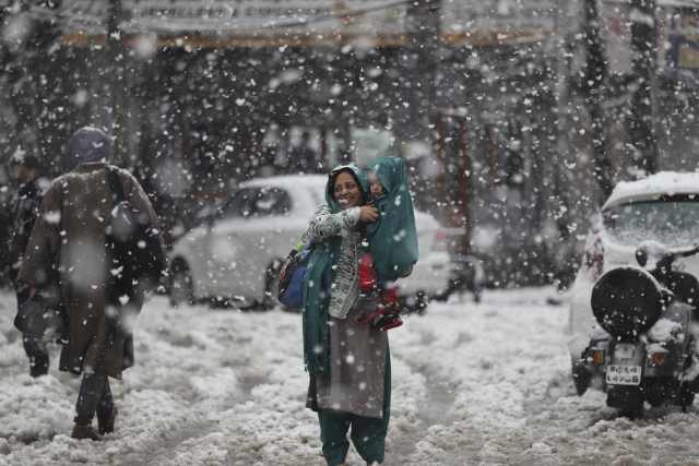 A Kashmiri woman covers her child with a shawl as they wait for transport in the snow in Srinagar. The region received its first snow on Wednesday, 6 November.