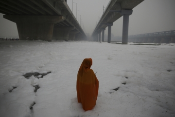 An Indian Hindu devotee performs rituals in Yamuna river, covered by chemical foam caused due to industrial and domestic pollution during Chhath Puja festival in New Delhi.