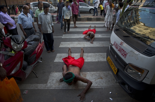 Indian devotees move while lying prostrate to reach the river Brahmaputra during Chhath Puja festival in in Gauhati.