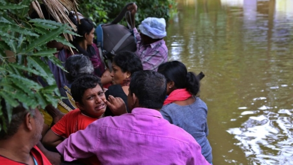 A boy cries as he sits in a boat after being rescued by volunteers in Kerala.