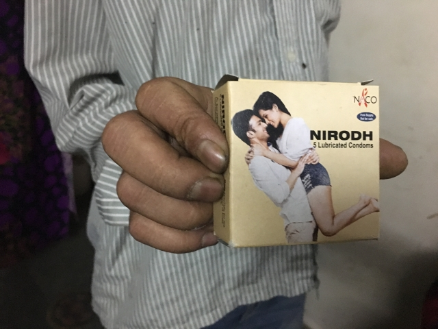 A man whose wife works as a sex worker in east Delhi holds a packet of condoms provided by NACO.