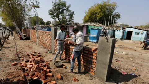 workers construct a wall in front of a slum in Ahmedabad